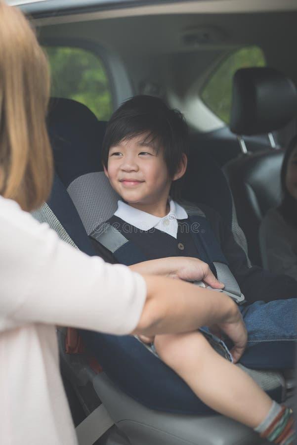 Kvinnafästandebarn med säkerhetssäkerhetsbältet i bil royaltyfri fotografi