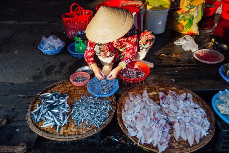 Kvinnaförsäljningar fiskar på morgonmarknaden, Vietnam arkivbild
