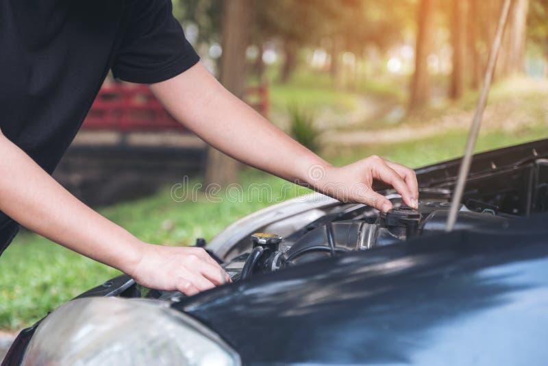 Kvinnaförsök till att fixa den brutna gamla bilen arkivbilder