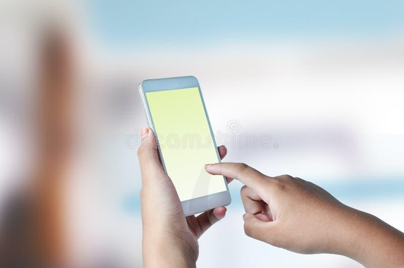 Kvinnafingerhandlaget på skärmen av mobiltelefonen, ordnar till för typ texten eller för kopieringsutrymme med härlig bakgrund arkivbilder