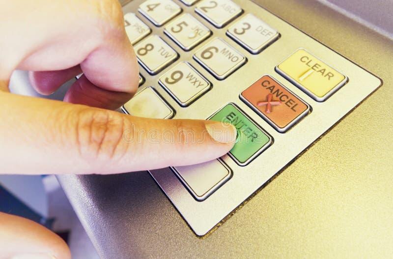 Kvinnafingret trycker på skriver in på ATM arkivbild