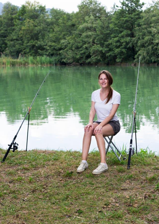 Kvinnafiske på en lake royaltyfri bild
