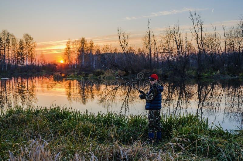 Kvinnafiske på solnedgången royaltyfri bild