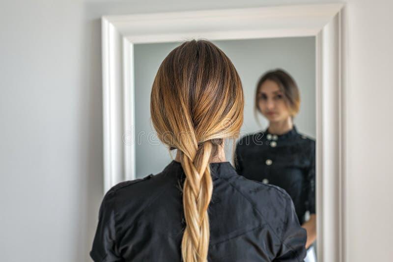Kvinnaflicka med ombrefrisyren i flätad tråd framme av spegeln arkivfoto