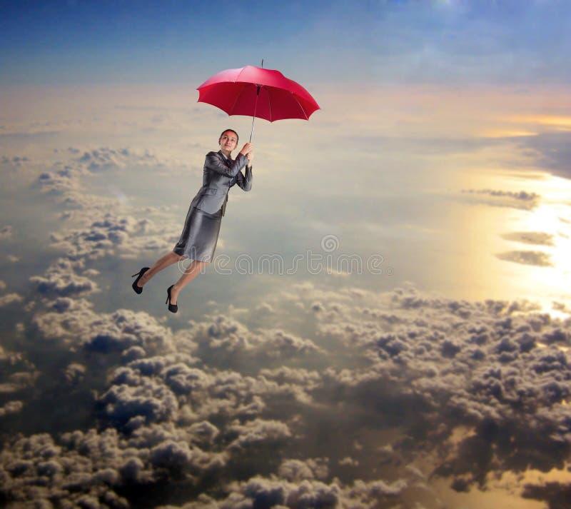 Kvinnaflyg i himlen med paraplyet arkivfoto