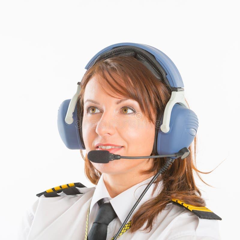 Kvinnaflygbolagpilot med hörlurar med mikrofon arkivbild