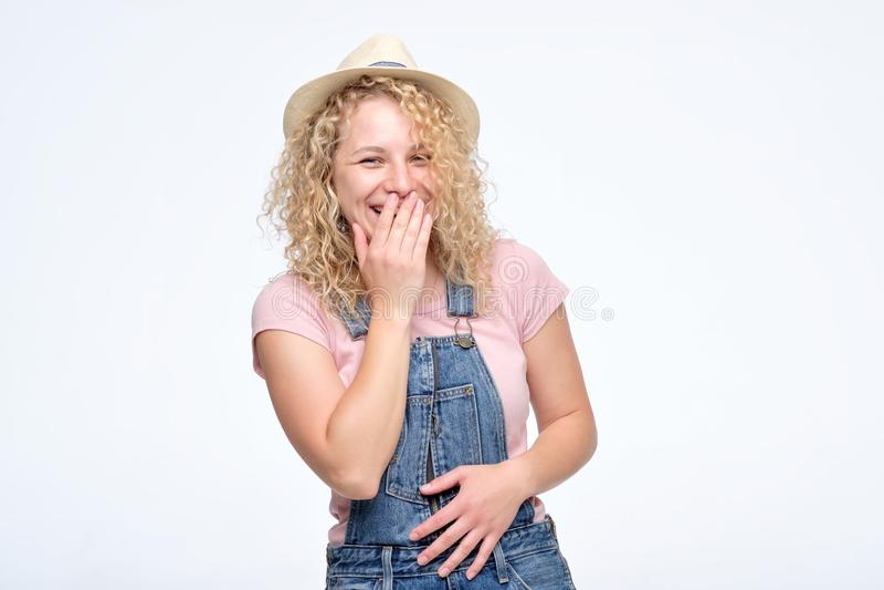 Kvinnafniss joyfully, täcker munnen, som försök stoppar att skratta arkivfoton