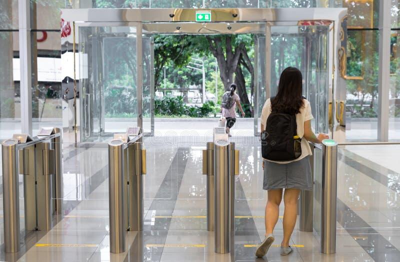 Kvinnafolk som ut går från säkerhet på en ingångsport med kontorsbyggnad för åtkomstskydd för nyckel- kort smart arkivfoto