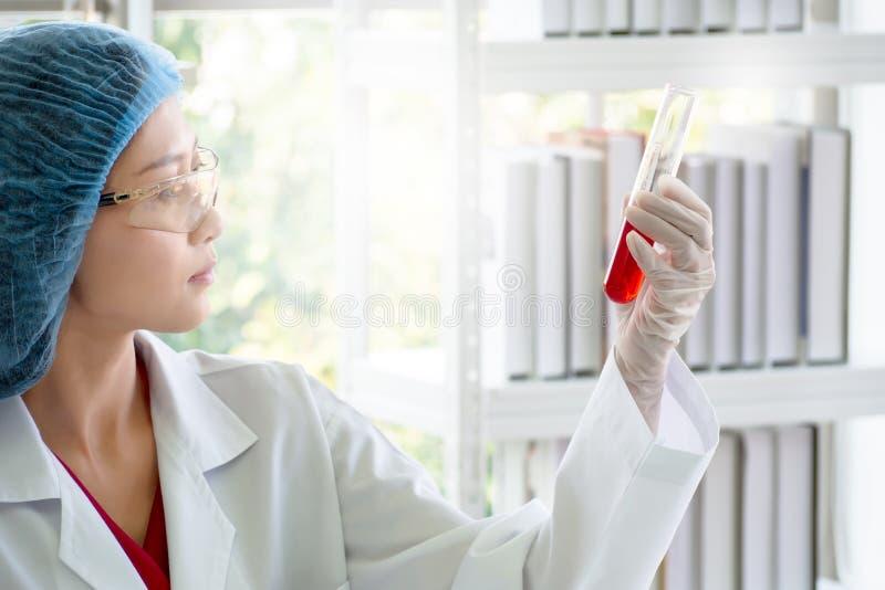 Kvinnaforskare eller kemist som kontrollerar den röda vätskevikten i provrör royaltyfria bilder