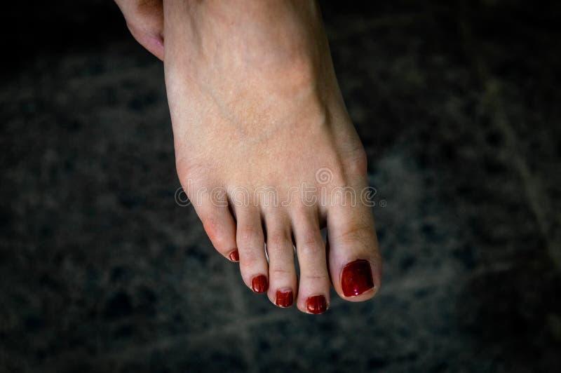 Kvinnafot med röd pedikyr arkivfoto