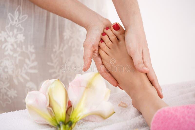 Kvinnafot på skönhetsalonggarneringar som får trevlig avslappnande massage royaltyfri foto