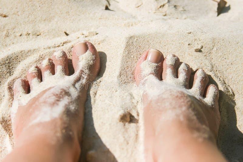 Kvinnafot som täckas med vit sand på stranden royaltyfri foto