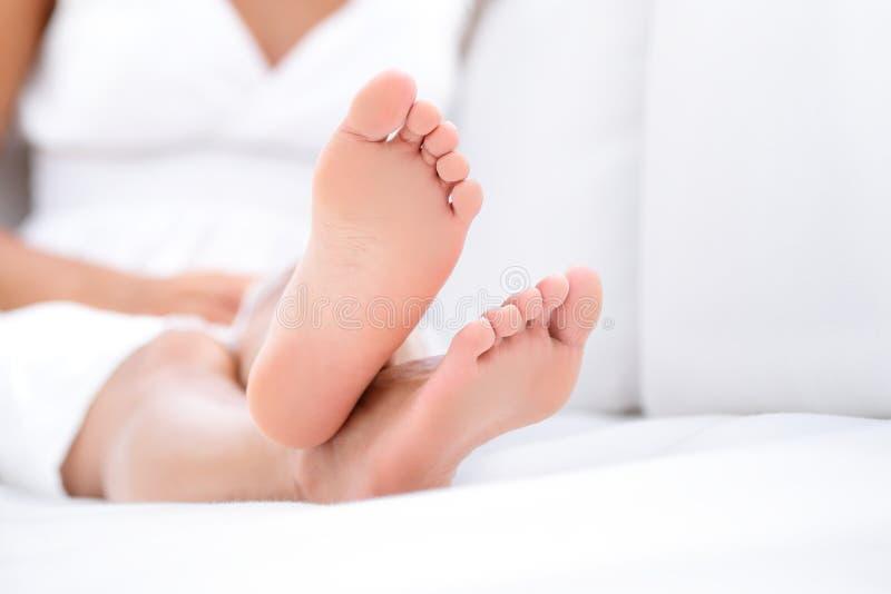 Kvinnafotcloseup - avslappnande soffa för barfota kvinna royaltyfria bilder