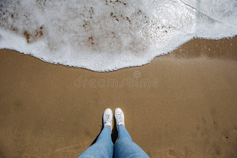Kvinnafoten beskådar med jeans från ovannämnt på stranden med sand och vågen som kommer i ramen arkivbilder