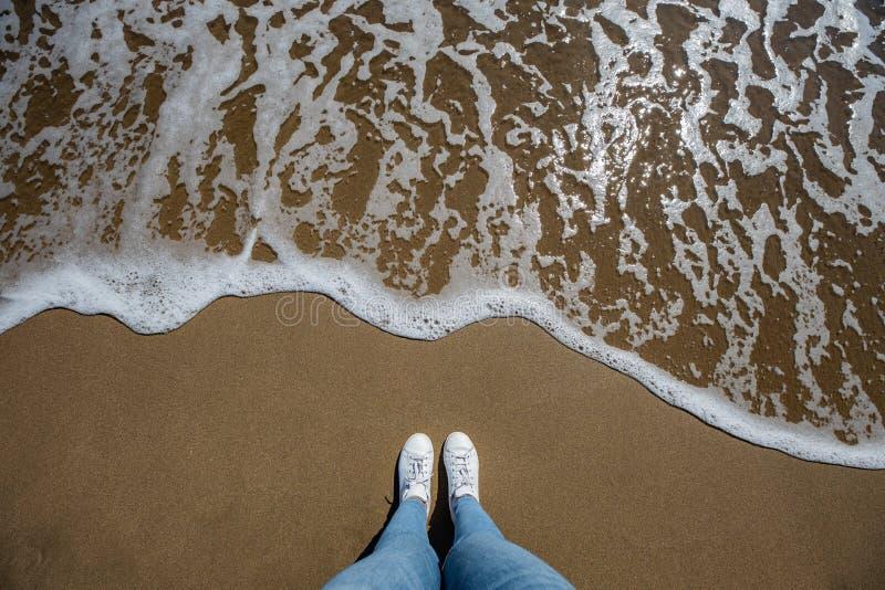 Kvinnafoten beskådar med jeans från ovannämnt på stranden med sand och vågen som kommer i ramen arkivfoto