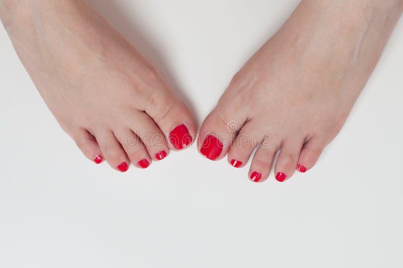 Kvinnafoten efter pedikyr med rött spikar arkivfoton