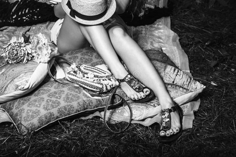 Kvinnafoten på gräs i plana sommarsandaler lutar på kuddar som hatten lägger på ben ovanför den svartvita sikten royaltyfri bild