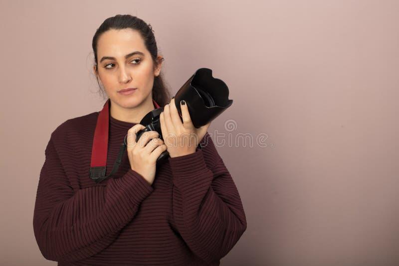Kvinnafotograf som rymmer en kamera och en lins royaltyfri foto