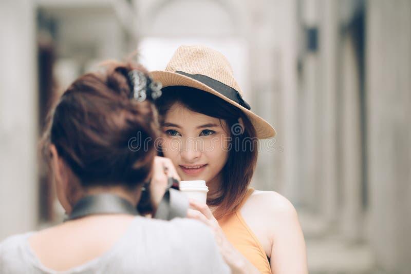 Kvinnafotograf som tar foto av den unga asiatiska modellflickaholdien arkivfoto