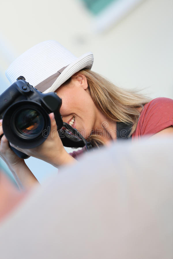 Kvinnafotograf som tar fotoet av en modell arkivbild