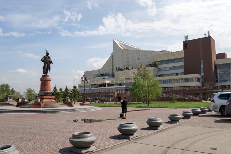 Kvinnafotografier en monument till statsman N P Rezanov på fyrkanten framme av den stora konserthallen i staden av Krasnoyarsk fotografering för bildbyråer