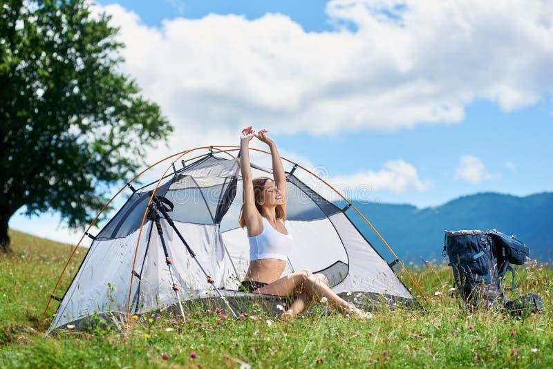 Kvinnafotvandrare i campa i bergen med ryggsäcken i morgonen royaltyfri bild