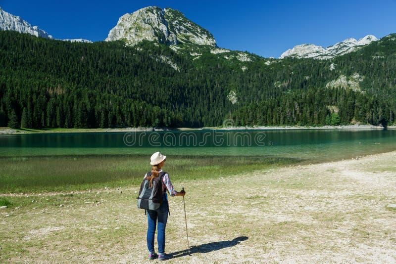 Kvinnafotvandrare med en ryggsäck och en gåpinne på den svarta sjön arkivfoton