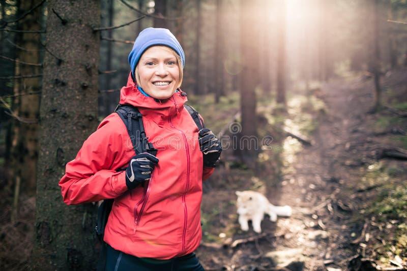Kvinnafotvandrare med hunden arkivfoton