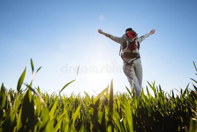 Kvinnafotvandrare med ryggsäckar som går till och med gräset fotografering för bildbyråer