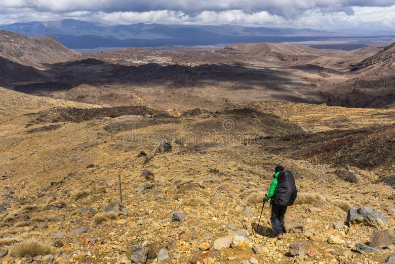 Kvinnafotvandrare med ryggsäcken som klampar på den Tongariro nationalparken arkivbild
