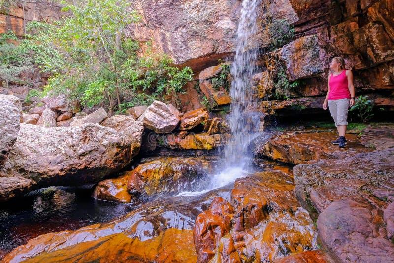 Kvinnafotvandrare på Cachoeira Da Primavera, vårvattenfall, Rio Lencois flod, Chapada Diamantina nationalpark, Brasilien royaltyfria bilder