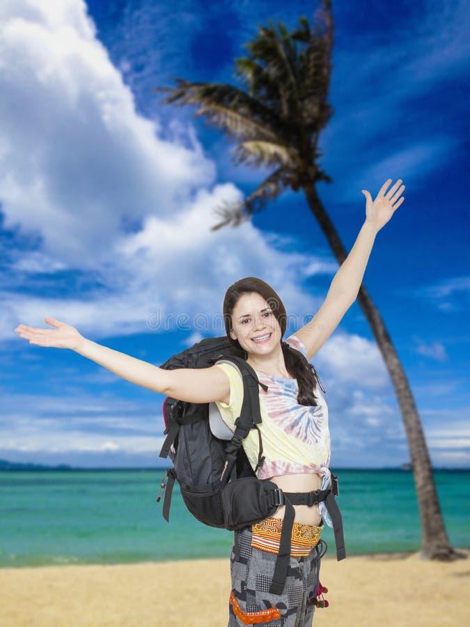 Kvinnafotvandrare som är lycklig att nå den tropiska stranden