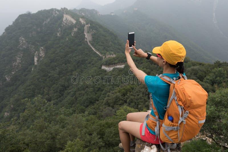 Kvinnafotvandrare som överst tar fotoet med den smarta telefonen av den stora väggen royaltyfria bilder