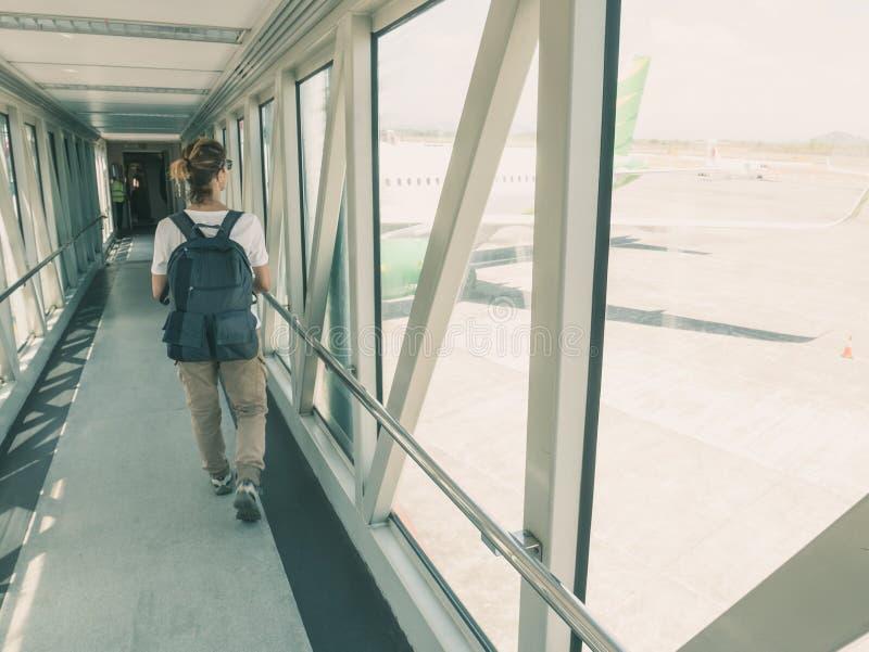 Kvinnafotvandrare som går för att utfärda utegångsförbud för för avvikelse i flygplatsterminal Fönstersiktsariplane som väntar, t arkivbilder
