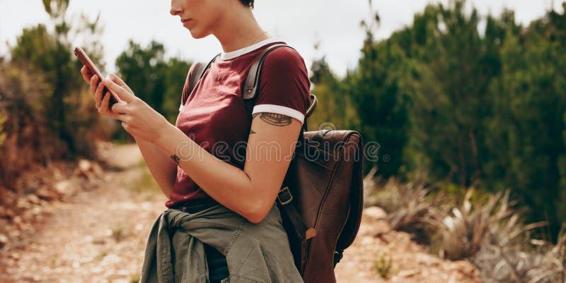 Kvinnafotvandrare som kontrollerar hennes mobiltelefon fotografering för bildbyråer