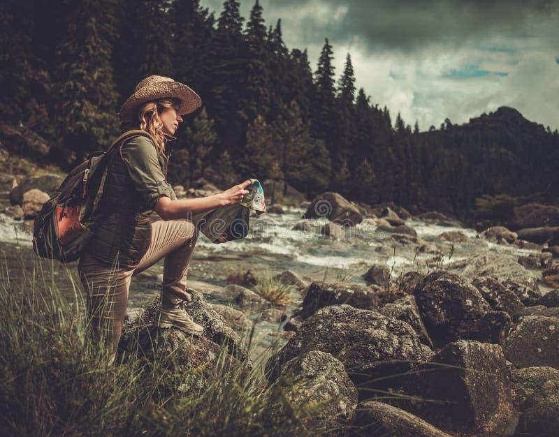 Kvinnafotvandrare som söker rätt riktning på översikt nära bergfloden royaltyfria bilder