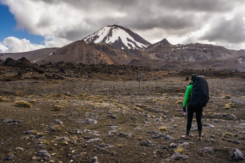 Kvinnafotvandrare som ser Mt Ngauruhoe i den Tongariro nationalparken arkivfoton