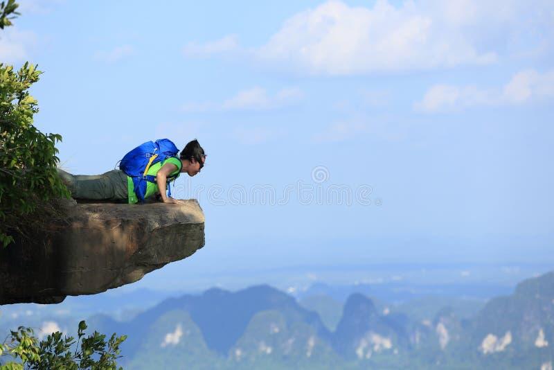Kvinnafotvandrare som ser ner på klippan för bergmaximum royaltyfria bilder