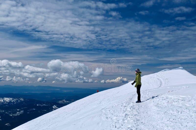 Kvinnafotvandrare som ser scenisk sikt fr?n berg?verkant Vinter som fotvandrar och kl?ttrar arkivbilder