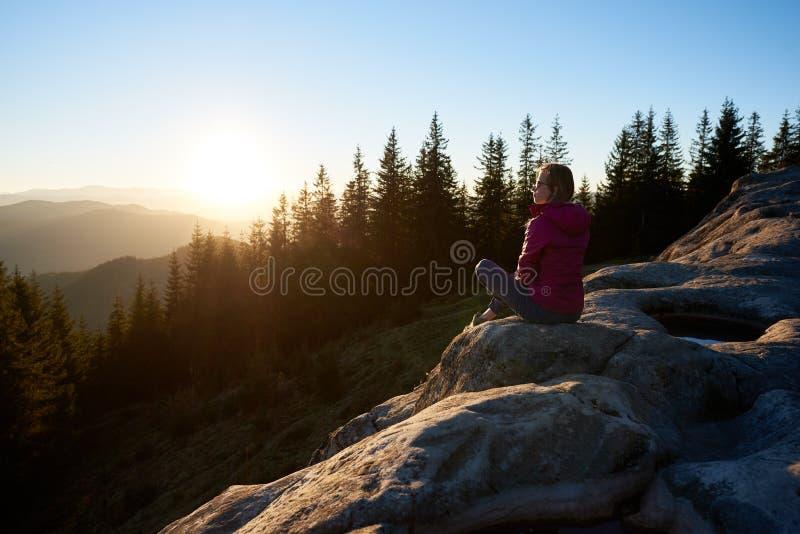 Kvinnafotvandrare som sitter på stenblocket i bergen på solnedgången royaltyfri fotografi
