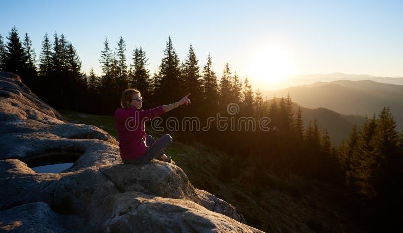Kvinnafotvandrare som sitter på stenblocket i bergen på solnedgången fotografering för bildbyråer