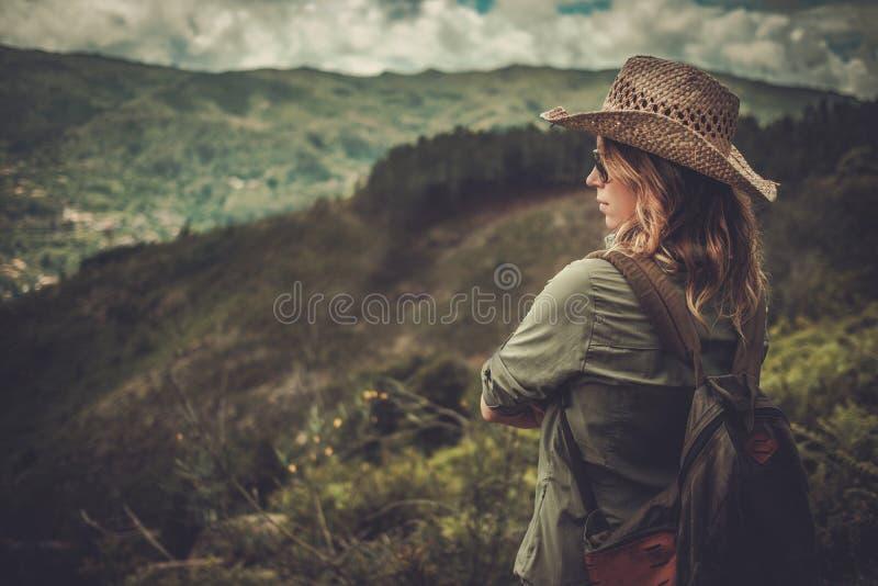 Kvinnafotvandrare som tycker om fantastiska dallandskap på en överkant av berget royaltyfri fotografi