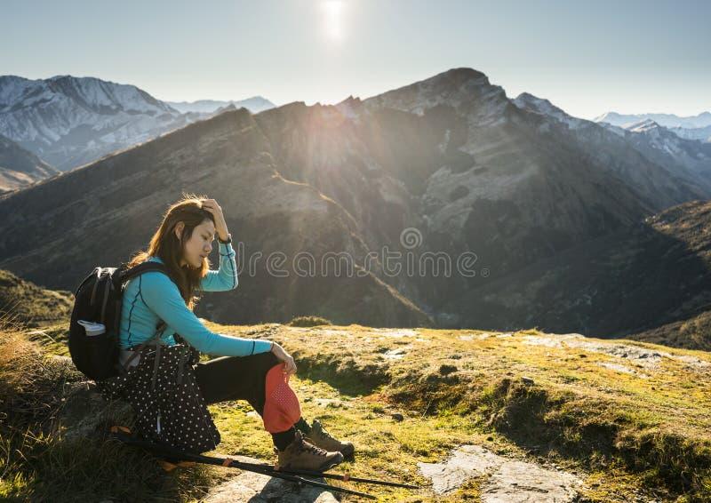 Kvinnafotvandrare som vilar på berget arkivfoton