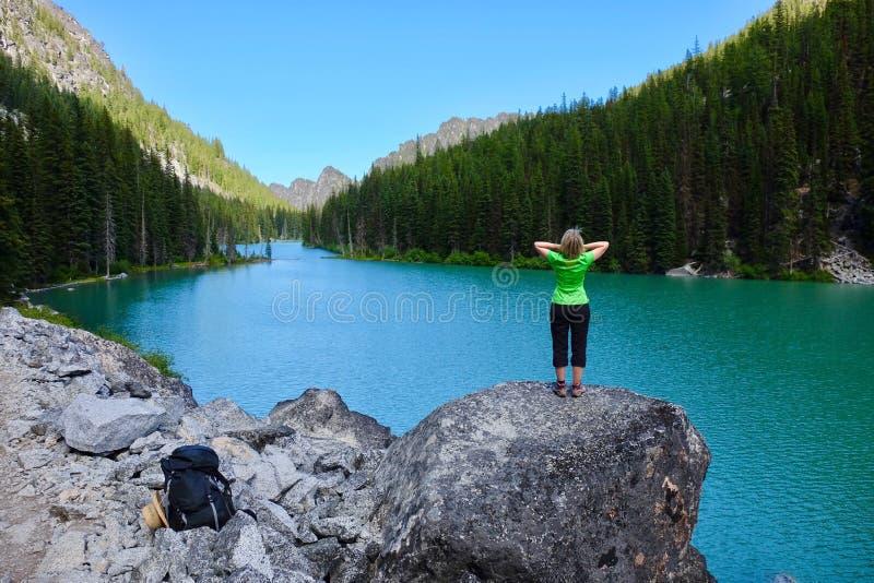 Kvinnafotvandrare vid den alpina blåa sjön arkivbild