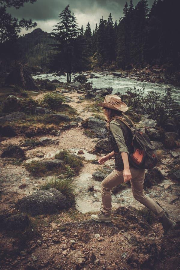 Kvinnafotvandrarebanhoppningen på stenarna near den lösa bergfloden royaltyfri foto