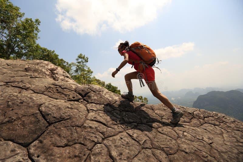 Kvinnafotvandrareklättringen vaggar på klippan för bergmaximumet royaltyfria foton