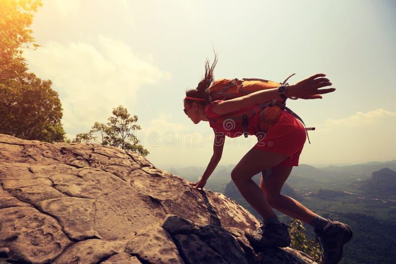 Kvinnafotvandrareklättringen vaggar på klippan för bergmaximumet arkivbilder