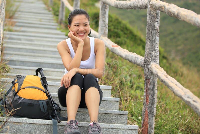 Kvinnafotvandraren sitter på bergtrappa royaltyfri foto