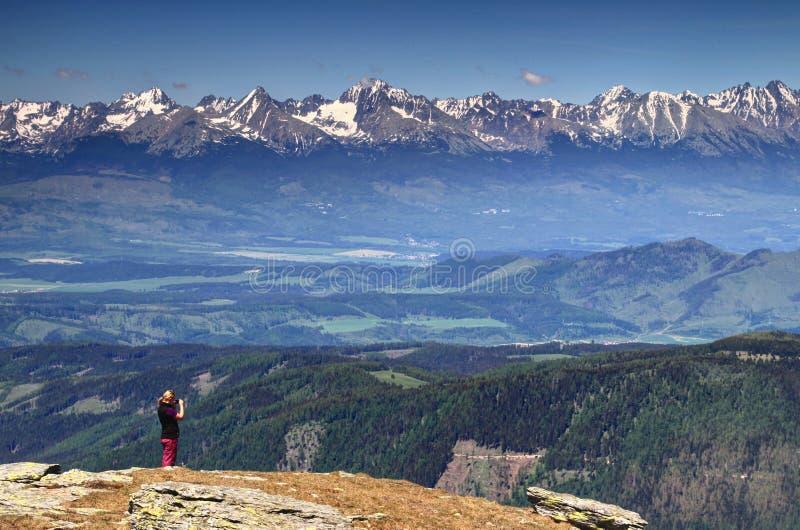 Kvinnafotvandraren som tar foto av snöig Vysoke Tatry, når en höjdpunkt Slovakien arkivbild