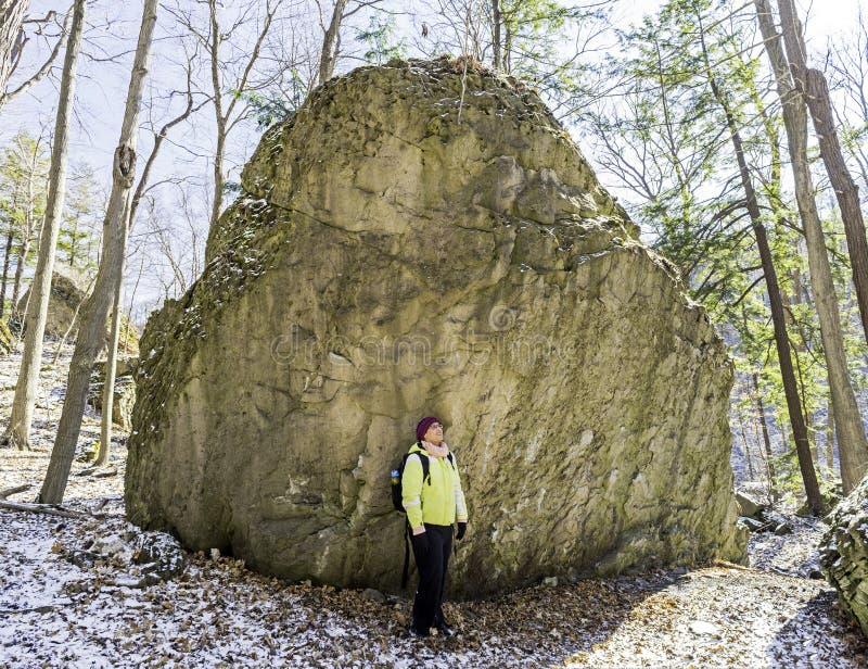 Kvinnafotvandraren stoppar bredvid den enorma stenblocket för att förundra sig på vildmarken royaltyfria bilder